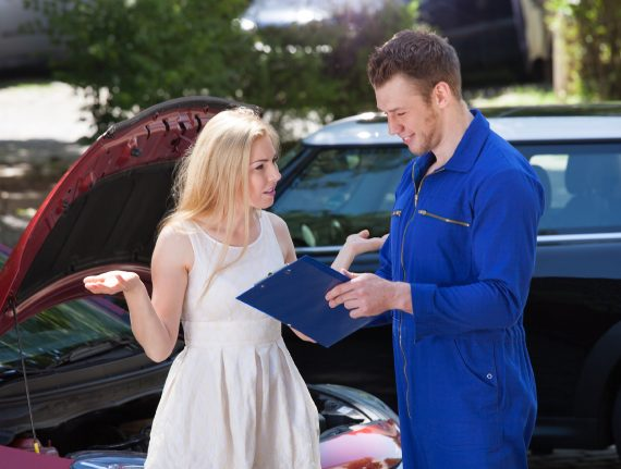 Young male mechanic showing clipboard to angry woman by breakdown car outdoors